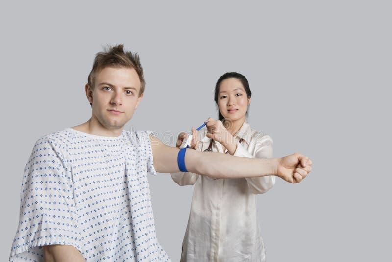 Retrato do paciente masculino com o doutor que prepara o para uma análise de sangue imagem de stock royalty free
