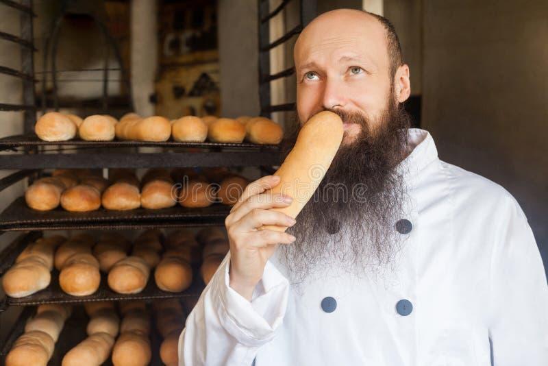 Retrato do padeiro adulto novo alegre com a barba longa na posição uniforme branca em sua fabricação, cheirando com o prazer fres imagem de stock