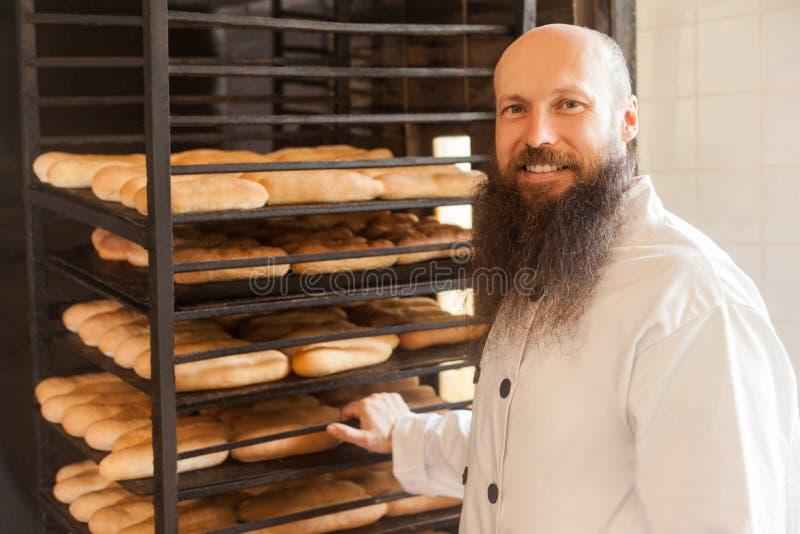 Retrato do padeiro adulto novo feliz com a barba longa na posição uniforme branca em seu local de trabalho e de prateleiras levan fotografia de stock royalty free