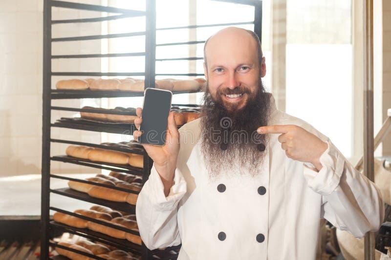 Retrato do padeiro adulto satisfeito do homem de negócios com a barba na posição uniforme branca na padaria e na ordem em linha d imagem de stock