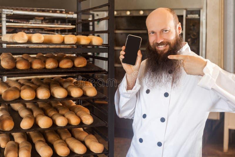 Retrato do padeiro adulto satisfeito do homem de negócios com a barba na posição uniforme branca na padaria e na ordem em linha d fotografia de stock