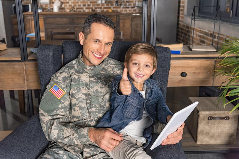 retrato do pai de sorriso no uniforme militar e no filho com tabuleta fotografia de stock royalty free