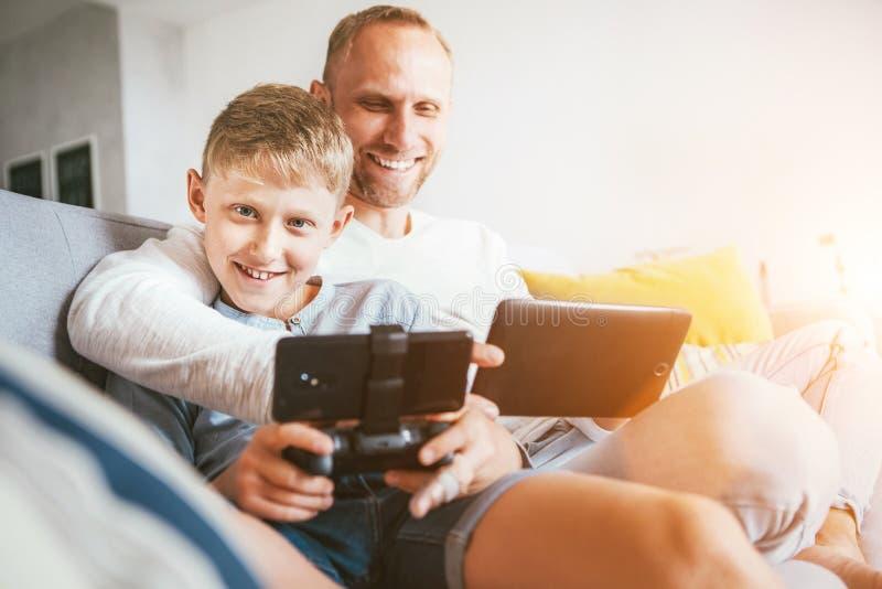 Retrato do pai e do filho com jogo dos dispositivos eletr?nicos Assento em casa na atmosfera acolhedor imagens de stock royalty free