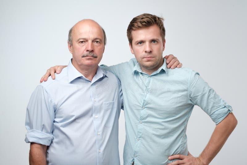 Retrato do pai maduro e do filho que estão com expressão séria na cara Bons relatios na família foto de stock