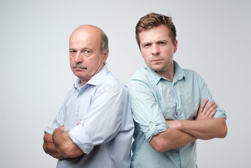 Retrato do pai maduro e do filho que estão com expressão séria na cara Bons relatios na família imagens de stock royalty free
