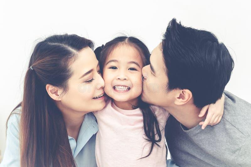 Retrato do paizinho atrativo e da mamã asiáticos que beijam o mordente da filha junto próximo acima no fundo branco isolado do es imagens de stock royalty free