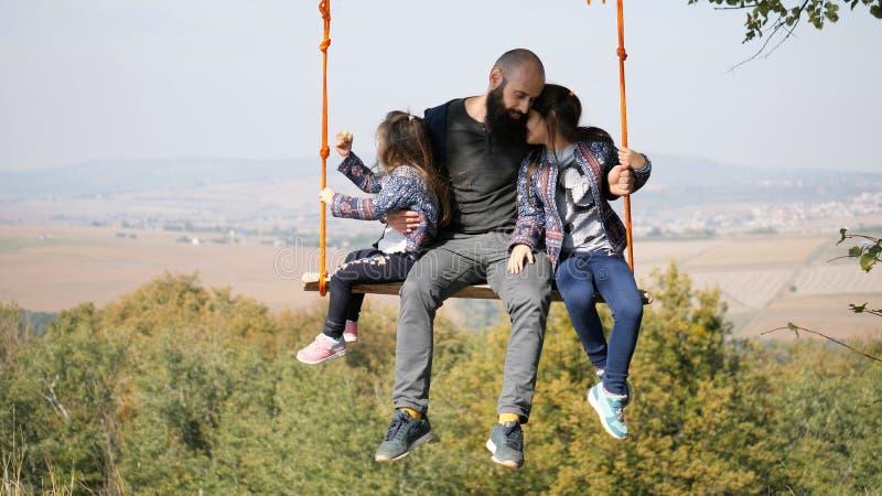 Retrato do paizinho que balança com filhas em um balanço sob uma árvore foto de stock royalty free