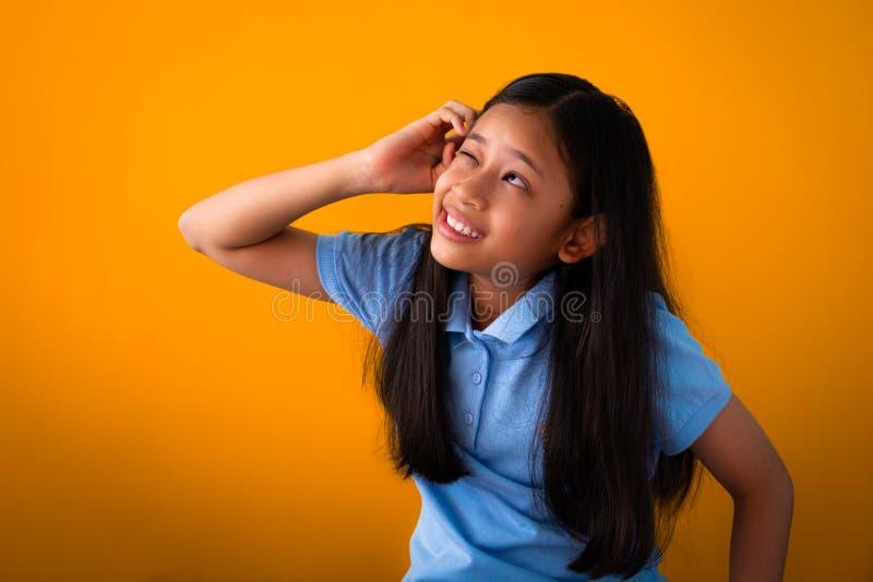 Retrato do pensamento bonito engraçado da menina isolado no fundo alaranjado fotografia de stock royalty free