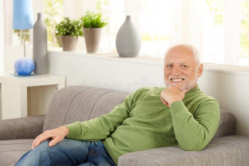 Retrato do pensionista no sofá imagens de stock