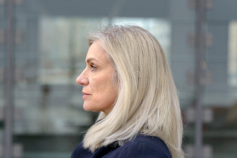 Retrato do perfil de uma mulher de meia idade loura fotografia de stock royalty free