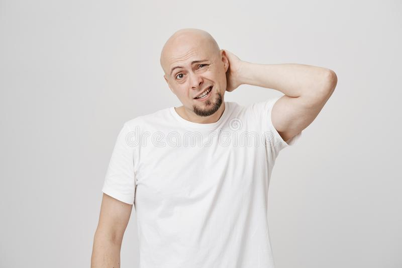 Retrato do pescoço de risco masculino farpado caucasiano calvo incomodado ao ser duvidoso, ao olhar de sobrancelhas franzidas e a foto de stock royalty free