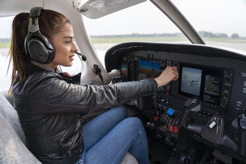 Retrato do piloto atrativo With Headset da jovem mulher na cabina do piloto fotos de stock