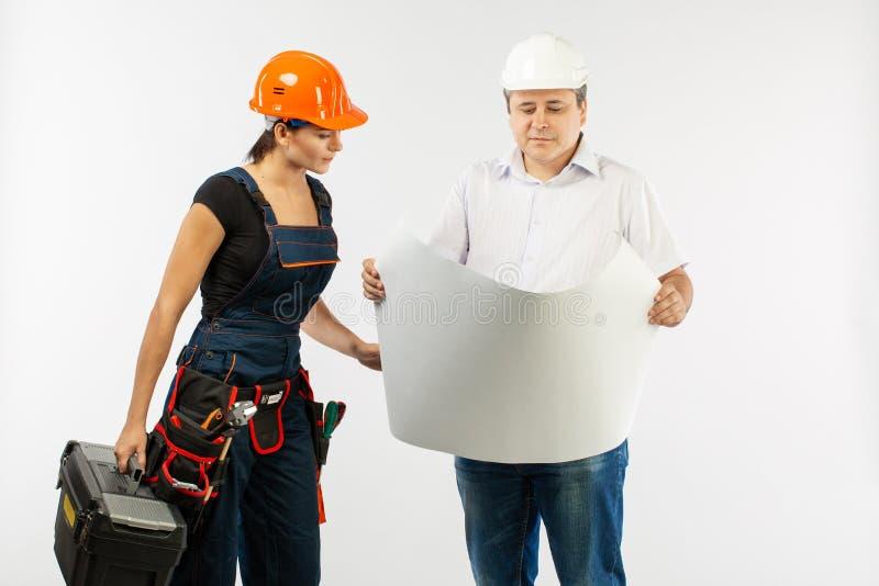 Retrato do plano masculino da construção de Woman Discussing do construtor de And do arquiteto contramestre que guarda o papel de fotos de stock royalty free