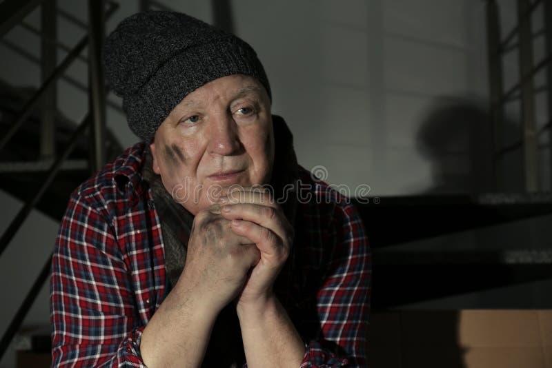 Retrato do pobre homem que senta-se em escadas dentro imagens de stock