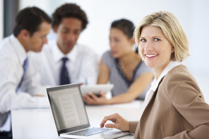 Retrato do portátil de utilização executivo fêmea com reunião do escritório no fundo imagem de stock royalty free