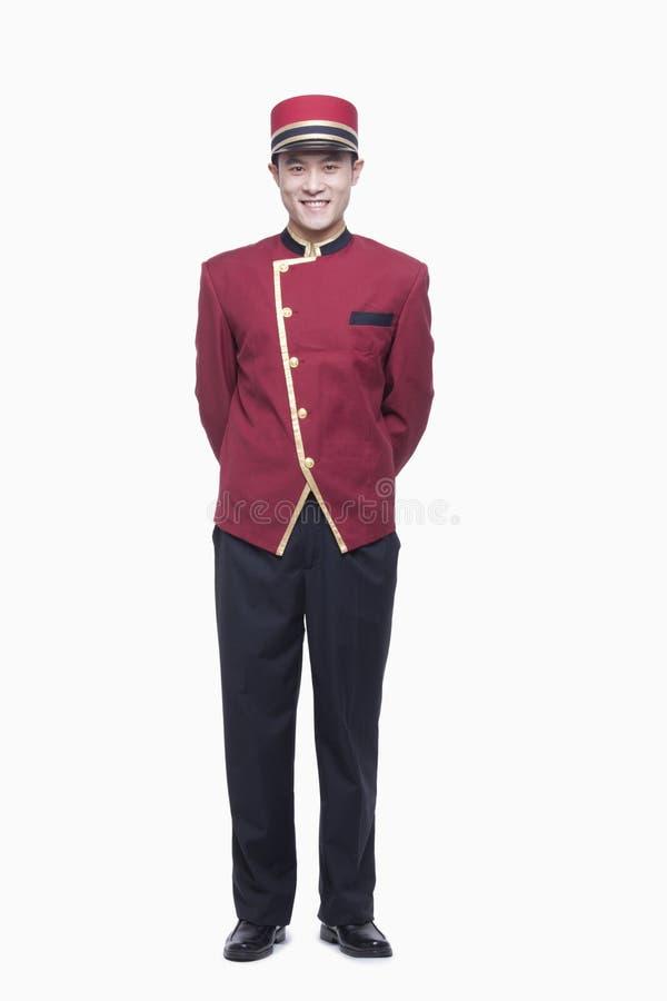 Retrato do porteiro de sorriso With Hands Behind traseiro, comprimento completo, tiro do estúdio imagem de stock