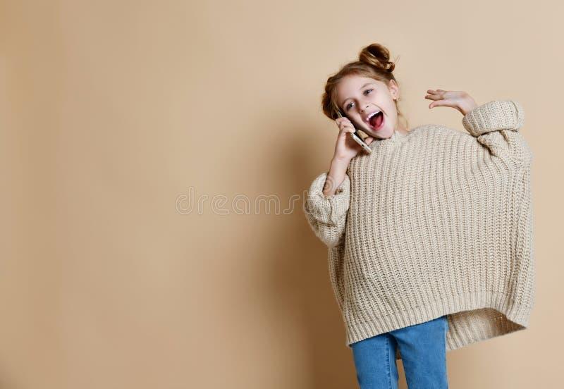Retrato do positivo do ` s da menina essa fala em um telefone celular fotos de stock
