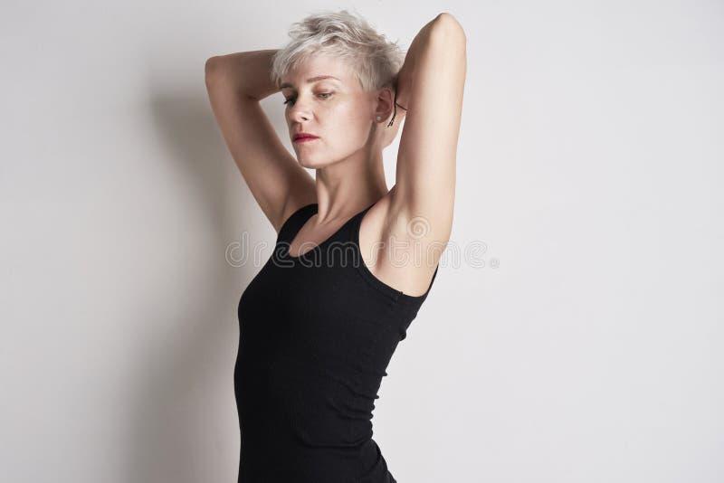 Retrato do preto vestindo da mulher bonita alta loura nenhum t-shirt da luva que levanta no fundo branco fotografia de stock