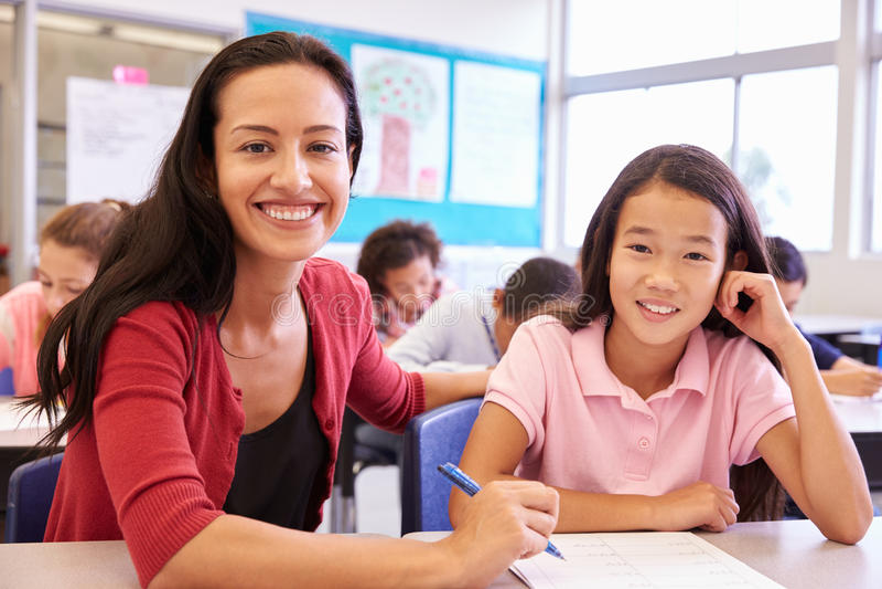 Retrato do professor com a menina da escola primária em sua mesa fotos de stock royalty free