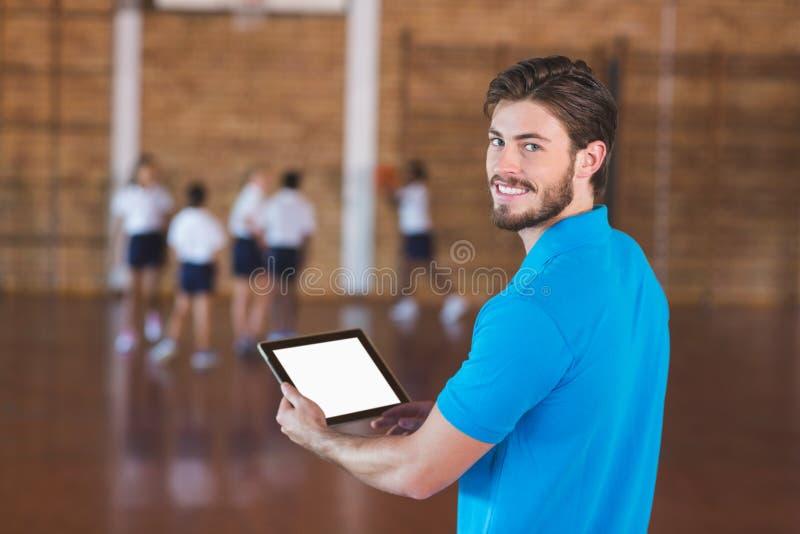 Retrato do professor dos esportes que usa a tabuleta digital imagens de stock royalty free