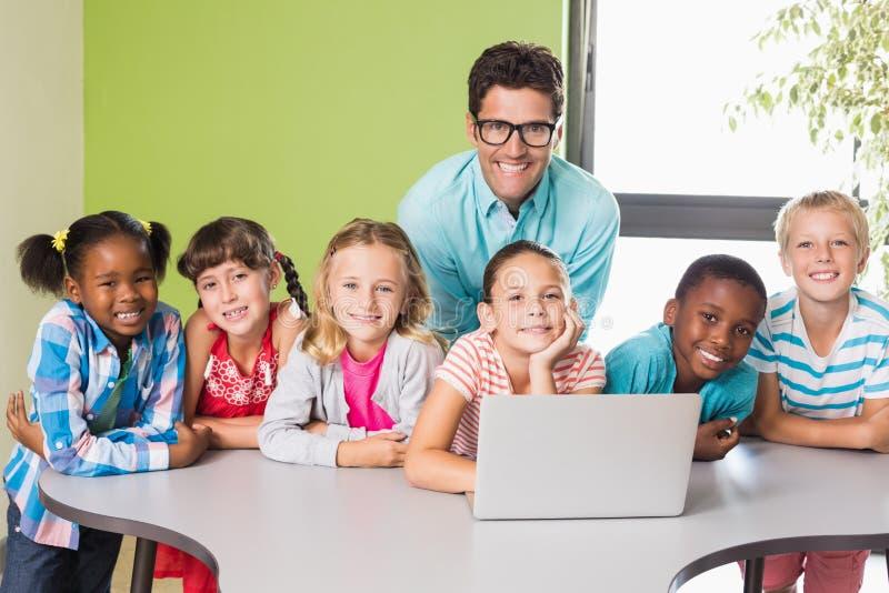 Retrato do professor e das crianças que usam o portátil na biblioteca fotos de stock