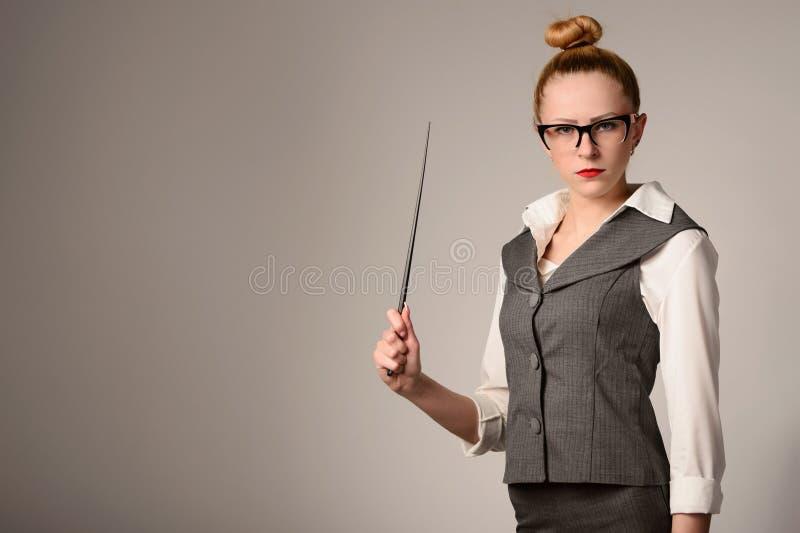 Retrato do professor novo que guarda o ponteiro Menina magro em um terno fotos de stock royalty free
