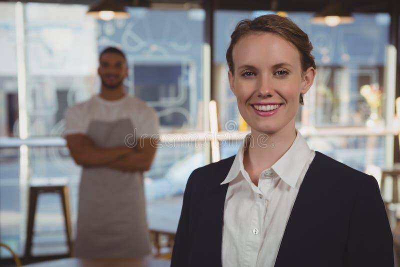 Retrato do proprietário fêmea com o garçom no fundo no café fotos de stock royalty free