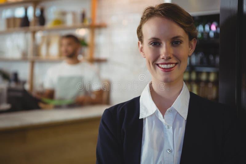 Retrato do proprietário feliz com o garçom no fundo no café foto de stock