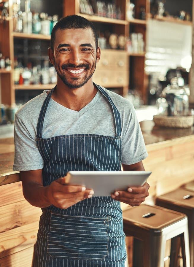 Retrato do proprietário masculino de sorriso do café que guarda a tabuleta digital foto de stock