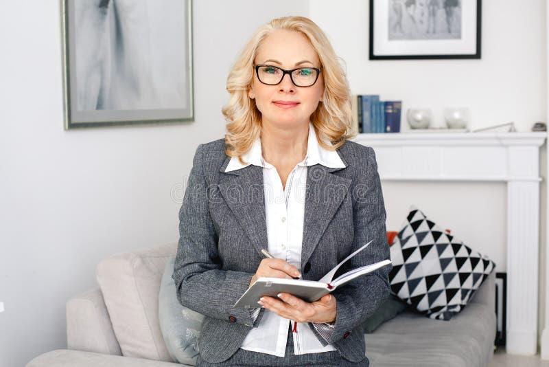 Retrato do psicólogo da mulher que senta-se no escritório domiciliário ocasional que guarda o organizador foto de stock