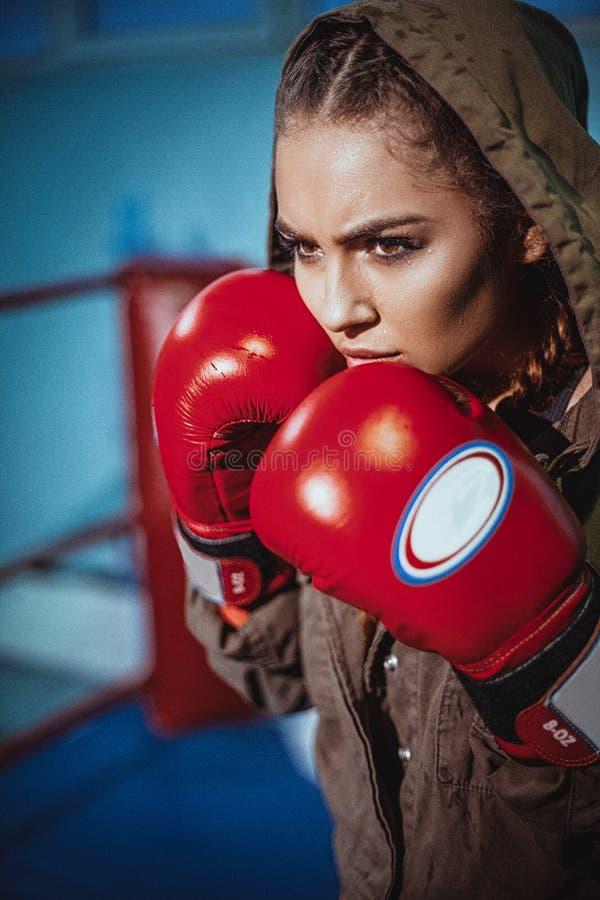 Retrato do pugilista fêmea no desgaste do esporte com posição de combate contra o projetor Menina loura da aptidão 'sexy' no desg foto de stock royalty free