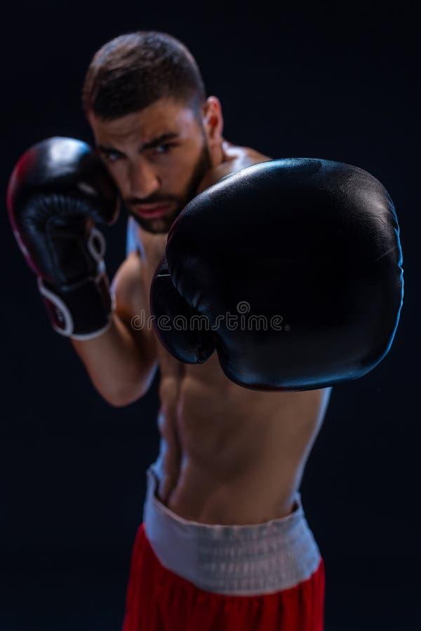Retrato do pugilista masculino resistente que levanta na posição do encaixotamento contra o fundo preto fotografia de stock royalty free