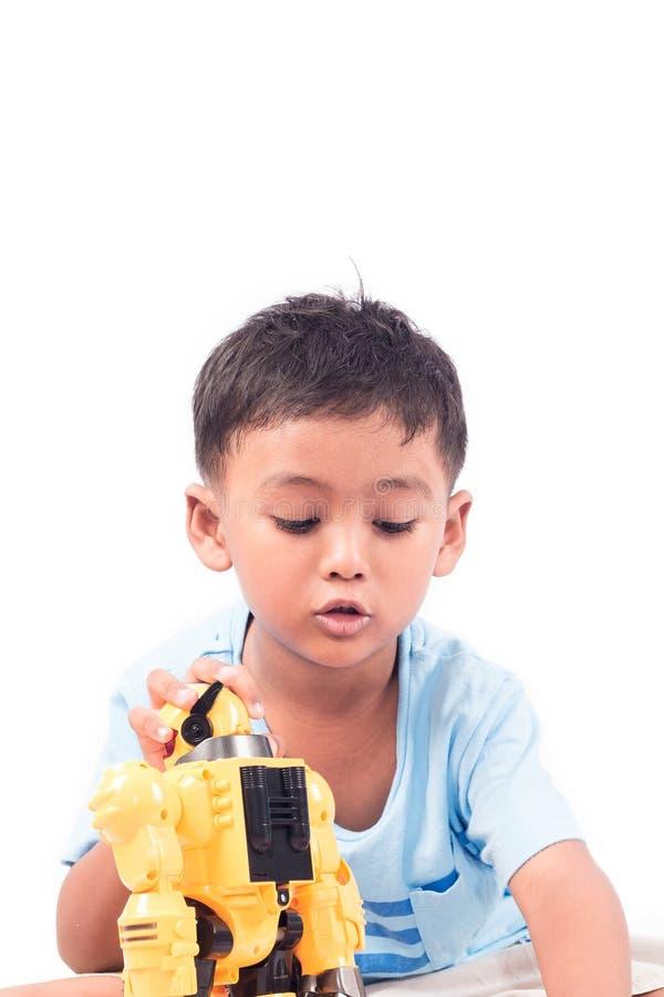 Retrato do rapaz pequeno asiático da criança bonito que joga o robô foto de stock royalty free