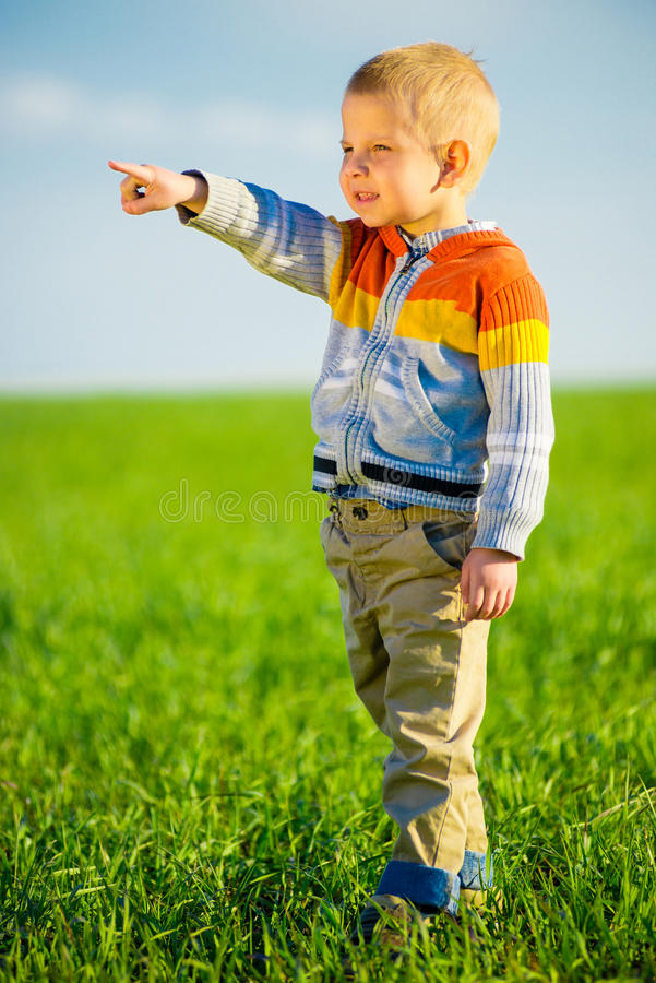 Retrato do rapaz pequeno bonito alegre feliz exterior no campo Apontando o conceito imagens de stock royalty free