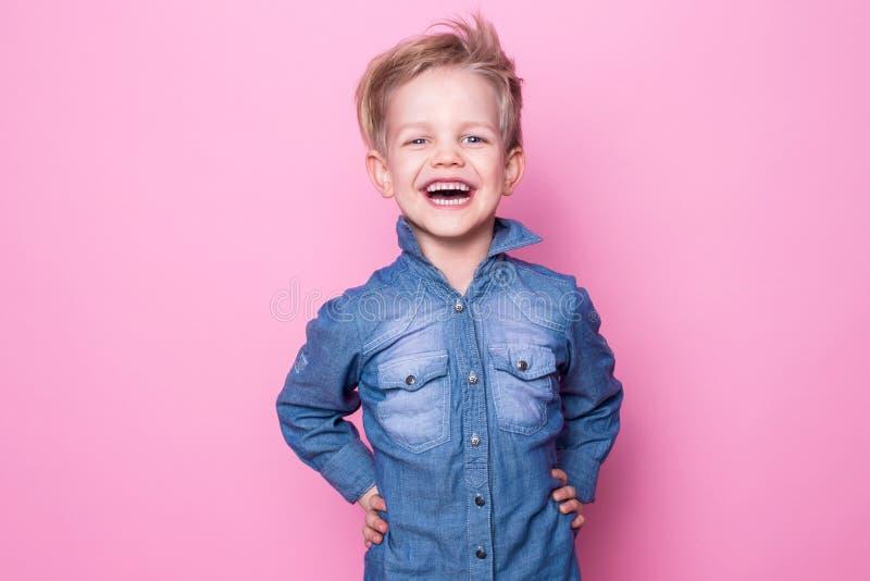 Retrato do rapaz pequeno bonito alegre feliz Retrato do estúdio sobre o fundo cor-de-rosa fotografia de stock