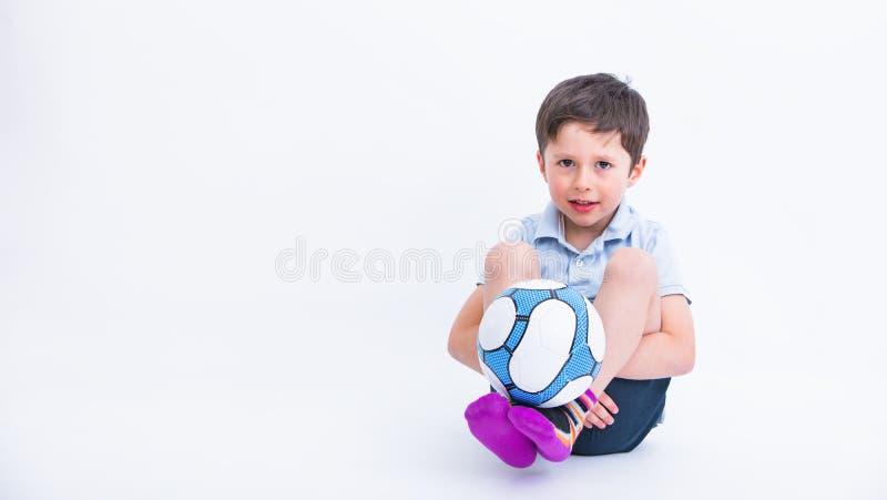 Retrato do rapaz pequeno bonito que joga o futebol, isolado no fundo branco do estúdio Criança adorável na atividade do esporte,  fotografia de stock