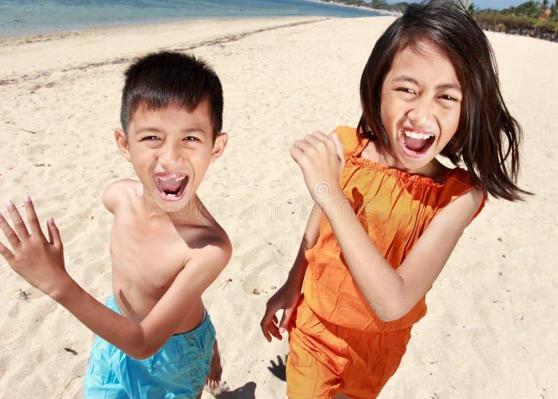 Retrato do rapaz pequeno feliz e da menina que correm na praia fotografia de stock
