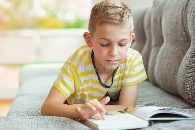 Retrato do rapaz pequeno inteligente com livro de leitura imagem de stock