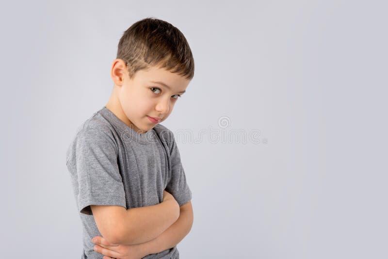 Retrato do rapaz pequeno irritado e triste no fundo branco imagem de stock royalty free