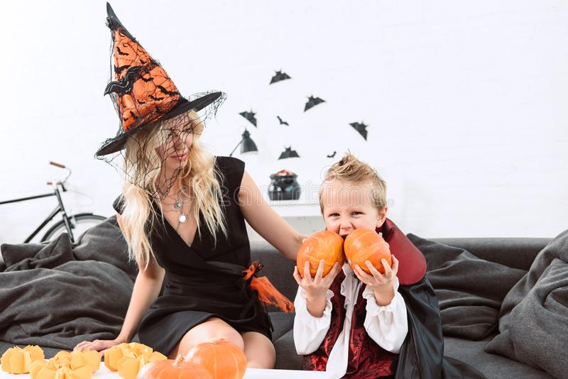 retrato do rapaz pequeno nas abóboras de mordedura do traje do Dia das Bruxas do vampiro que sentam-se no sofá com mãe imagens de stock