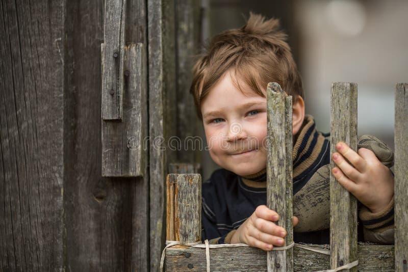 Retrato do rapaz pequeno perto de uma cerca na vila feliz imagem de stock