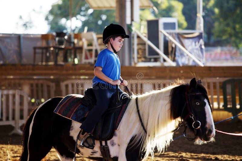 Retrato do rapaz pequeno que monta um cavalo Primeiras lições da equitação fotos de stock royalty free