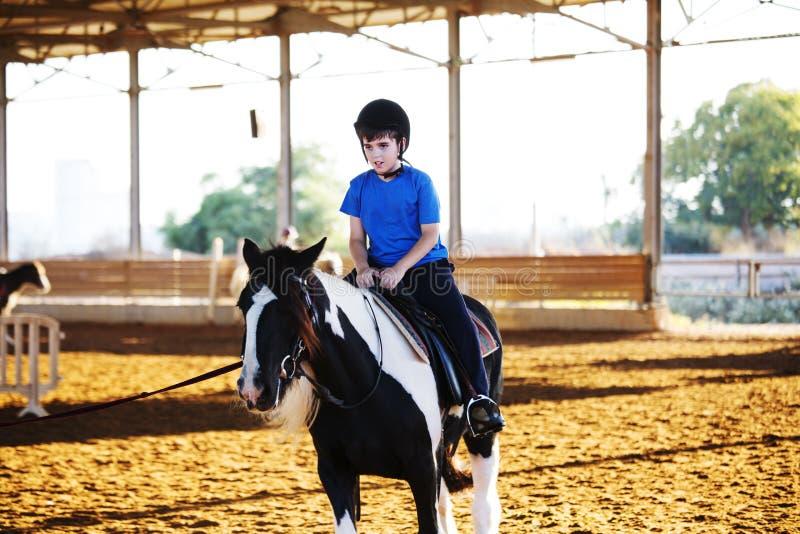 Retrato do rapaz pequeno que monta um cavalo Primeiras lições da equitação foto de stock royalty free