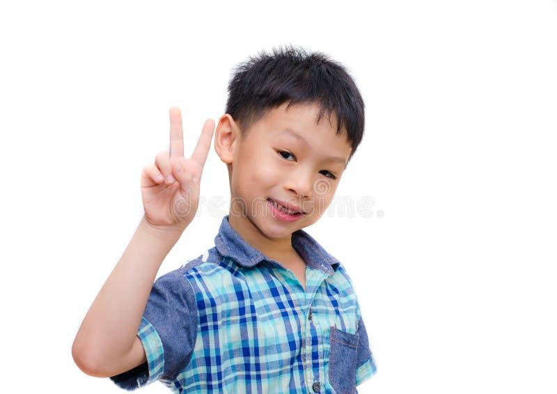 Retrato do rapaz pequeno que mostra o sinal da mão da vitória foto de stock