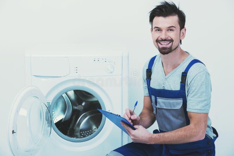 Retrato do reparador de sorriso novo que está com sua prancheta imagem de stock royalty free