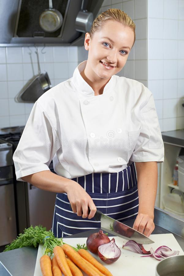 Retrato do restaurante fêmea Kitch de Preparing Vegetables In do cozinheiro chefe imagem de stock