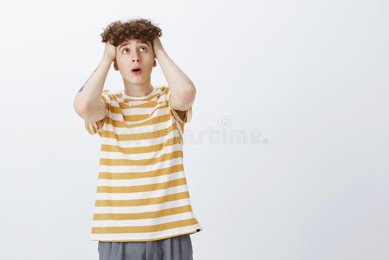 Retrato do sentimento adolescente incomodado e drenado do indivíduo referido e confundido guardando as mãos na boca aberta do cab fotografia de stock royalty free