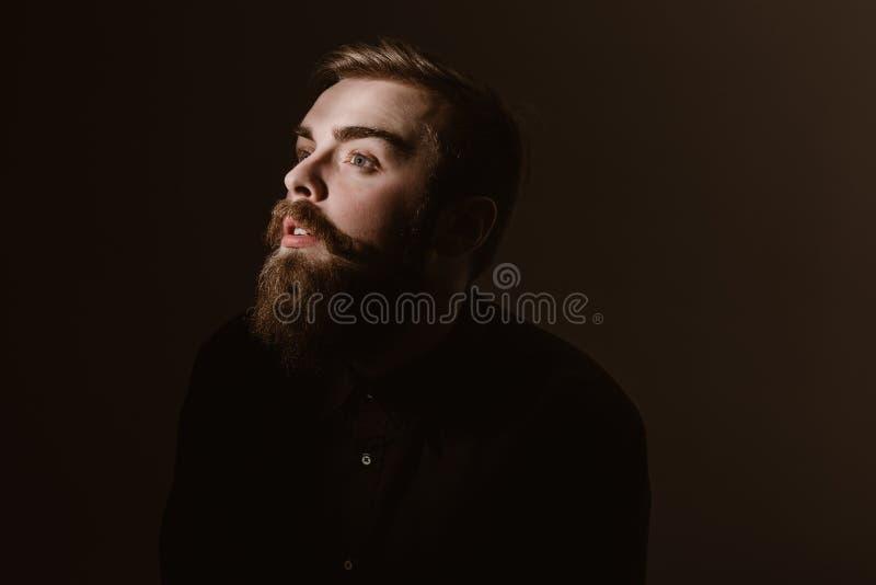 Retrato do Sepia de um homem pensativo com uma barba e um penteado à moda vestidos na camisa preta no fundo escuro foto de stock