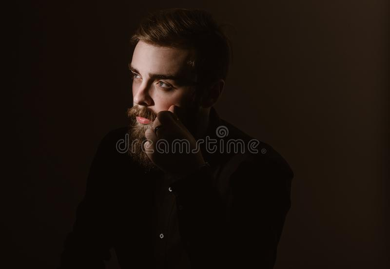 Retrato do Sepia de um homem pensativo com uma barba e um penteado à moda vestidos na camisa preta no fundo escuro imagem de stock royalty free