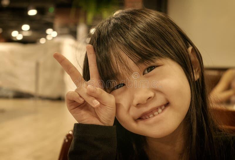 Retrato do Sepia de uma menina asiática pequena com gesticular um sinal de paz fotos de stock royalty free